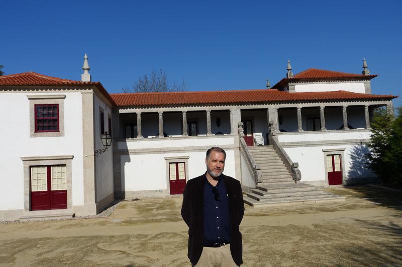 NOVOの生産者パウロさん、築500年の家の前で
