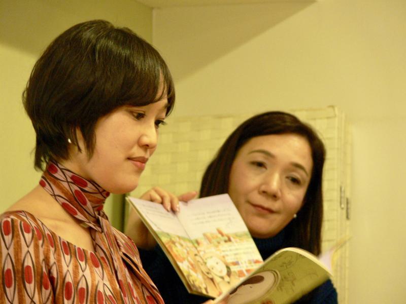 見守る高岡さん(右)とルミさんの朗読(左)