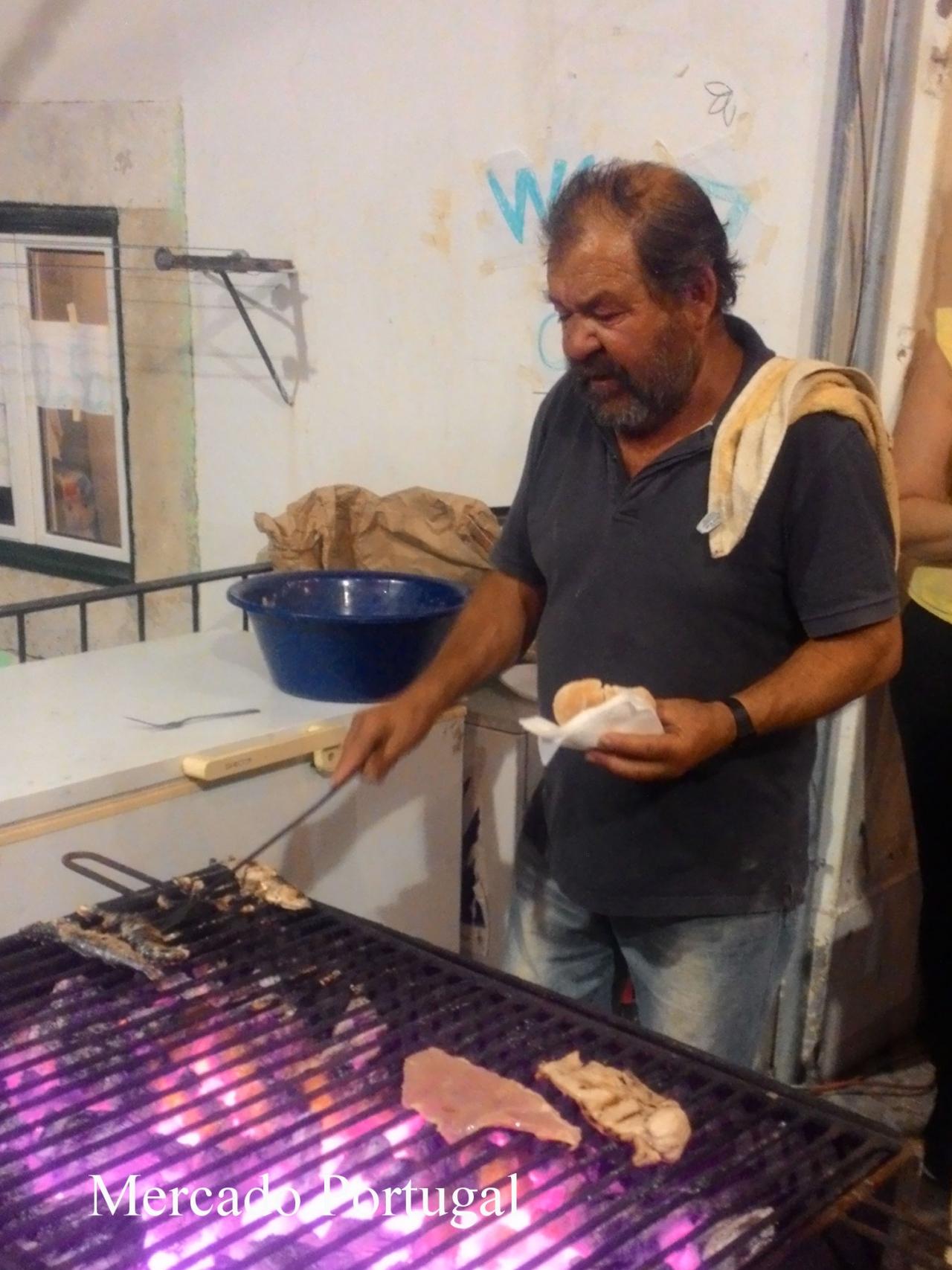 おじさんもパンを片手にいわしを焼きます。大忙し