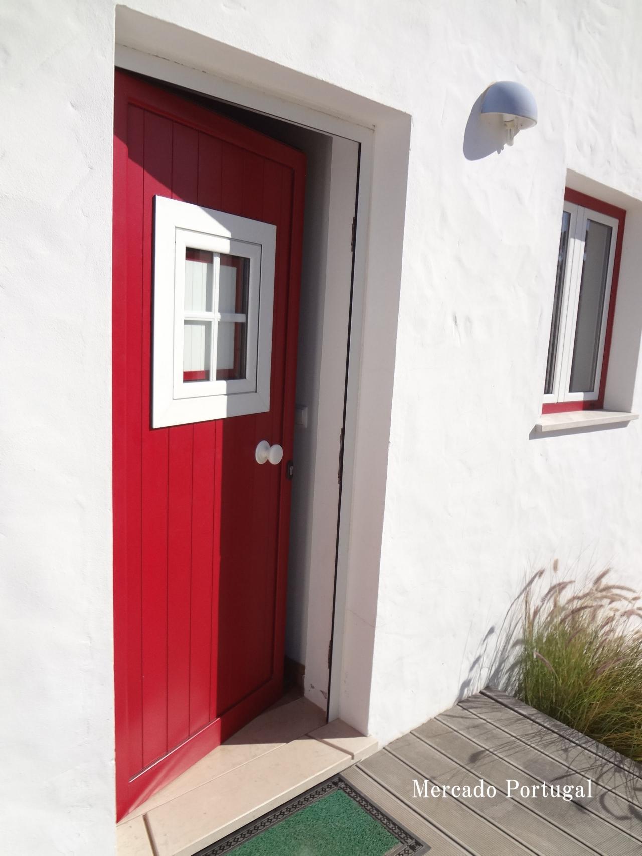 白い壁と赤いドア。ポルトガルの青い空によく映えます。